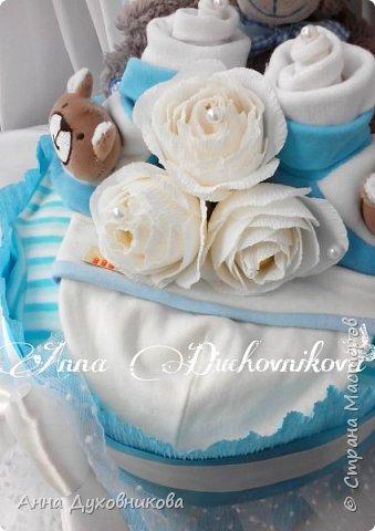 Всем привет. Сегодня покажу вам свои первые памперсные тортики. Первый делала в подарок. Основу из памперсов обернула пеленкой хб, сверху кофточка и шапочка. В пинеточки посадила розочки из носочков. Ну и розы с конфетами. фото 2
