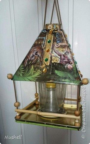 Доброе время суток всем мастерам! Вот такая кормушка для птиц получилась у меня из жестяной коробочки-пирамидки от новогоднего подарка, который был получен в цирке. Так сказать, от братьев Запашных- на крышке так и написано.  Мне понадобились: коробка от подарка, фанерка, шнур бельевой, стакан от блендера, палочки бамбуковые, бусины деревянные, клей-секунда, клей-титан,  дрель,  бутылка пластиковая с крышкой, скрепки и конечно же семечки! фото 1