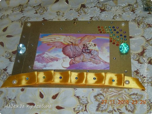 Вот такую рамочку я сделала для братишки. Ему 8 лет и он очень любит все золотое, блестящее и похожее на драгоценности. И рамочка получилась соответствующая. Вырезала из пивного картона два прямоугольника. в маленьком прямоугольнике сделала прямоугольное отверстие для фото, которое вставляется сверху. Покрасила краской цвета золото и залачила. Приклеила ленточку тоже цветом под золото, наклеила стразы, полубусины и большие брюллики. фото 2