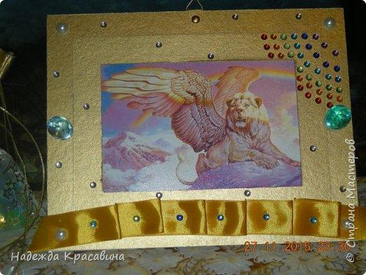 Вот такую рамочку я сделала для братишки. Ему 8 лет и он очень любит все золотое, блестящее и похожее на драгоценности. И рамочка получилась соответствующая. Вырезала из пивного картона два прямоугольника. в маленьком прямоугольнике сделала прямоугольное отверстие для фото, которое вставляется сверху. Покрасила краской цвета золото и залачила. Приклеила ленточку тоже цветом под золото, наклеила стразы, полубусины и большие брюллики. фото 1
