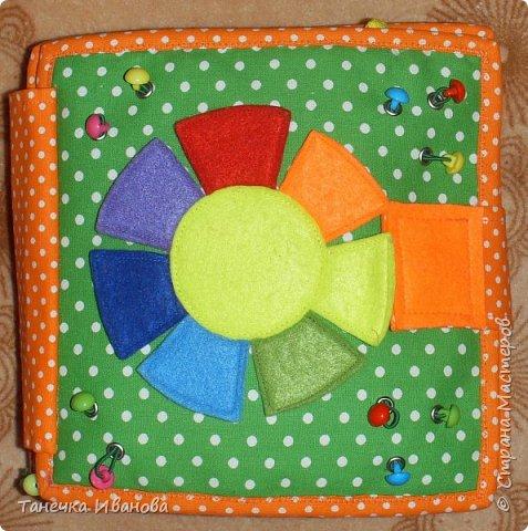 Моя книжка. Ткань- бязь в горошек и однотонная. Детальки все из фетра, двойные, простроченные. Странички размером 20*20, внутри синтепон нетолстый. Обложка- цветик -семицветик. Изучаем цвета. Пуговки разноцветные- перетяжки, на резинке шляпной ( круглой). Пуговок 10 штук. Соединены резинкой попарно. Люверсы. Застежка из той же ткани, магнитная.  фото 1