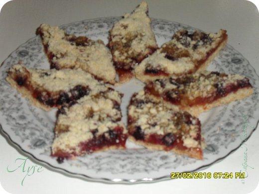 Это печенье я испекла по рецепту Наташи (Нанатик) - http://stranamasterov.ru/node/844463?tid=291. Наташа, спасибо тебе огроменное!!!))) Знаю, что многие уже готовили по этому твоему рецепту) Как раз есть повод напомнить тем, кто готовил, и дать узнать его тем, кто, возможно, упустил его случайно. Теперь я буду рецепты, понравившиеся мне, сохранять в свой блог, чтоб были под рукой. Прельстила скорость приготовления, доступность продуктов и необходимость реализации смородины. Да-да, в варенье я добавила замороженную смородину примерно 1:1. Продукты как у Наташи (а в скобках с моей небольшой корректировкой под меня): -100г сливочного масла (брала половину пачки 180гр, то есть 90гр) -400г муки пшеничной (так и получилось; делала дважды и оба раза ушло 400гр) -1 яйцо -100г сахарной пудры (брала примерно 80-90гр сахара, не пудры) -примерно чуть больше половины стакана повидла (у Наташи абрикосовое, у меня в первый раз был грейпфрутово-банановый курд с замороженной черной смородиной 1:1, во второй раз - яблочно-грушевое варенье опять же с замороженной смородиной 1:1).  -0,5 ч.л. соды -соль щепотка -сливочное масло для смазывания формы (в форму налила 1ст.л. растительного масла и смазала обильно силиконовой кисточкой). Сразу хочу уточнить, что продукты указаны из расчета не на большой противень. Я готовила в толстостенной сковороде (мне удобно в ней, всегда отлично получается выпечка и не подгорает) диаметром 30см. Технология приготовления описана у Наташи. Все продукты кроме начинки смешать в крошку (я не использовала миксер, вначале лопаточкой, потом руками), выложить в смазанный противень половину крошки (у Наташи половину, я же клала 2/3 или даже немного больше), рукой утрамбовать (кладешь ладошку сверху и сразу же крошка отлично прижимается за одно нажатие), сверху выложить начинку и посыпать оставшейся крошкой. Выпекать 15-20 минут при температуре около 180градусов (или смотреть по своей духовке). фото 1