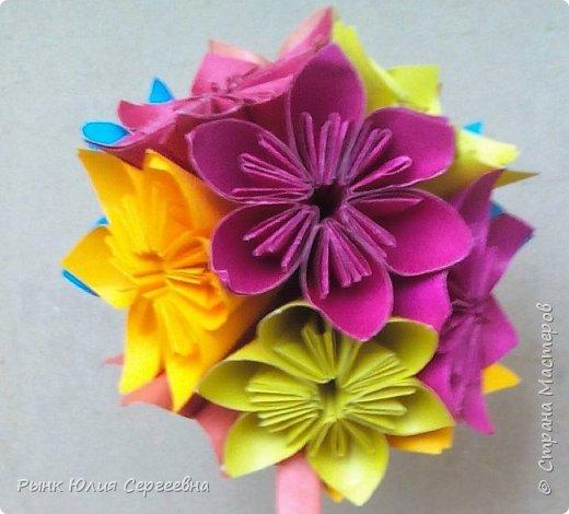 Один из видов оригами - кусудама. Кусудама – это цветочный шар из бумаги. Техника его изготовления популярна во всем мире. Кусудамы делают поэтапно. Вначале создаются объемные лепестки, затем их объединяют в один большой цветок. Склеенные между собой цветки образуют красивый и объемный шар.  фото 1