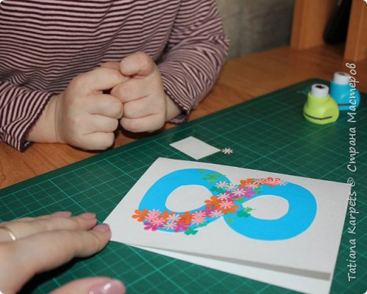 Для открыток мы использовали: плотную белую бумагу, цветную бумагу, шаблоны, фигурные дыроколы, ножницы, клей. Перед тем как делать аппликацию, я подготовила всё необходимое: из плотной белой бумаги сделала основу для открыток, вырезала из цветной бумаги восьмёрки, вырезала и собрала объемные цветы, с помощью фигурных дыроколов сделала маленькие листики и цветочки.  Остальное мы делали уже вместе с дочкой.  фото 8