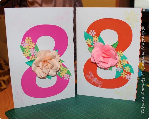 Для открыток мы использовали: плотную белую бумагу, цветную бумагу, шаблоны, фигурные дыроколы, ножницы, клей. Перед тем как делать аппликацию, я подготовила всё необходимое: из плотной белой бумаги сделала основу для открыток, вырезала из цветной бумаги восьмёрки, вырезала и собрала объемные цветы, с помощью фигурных дыроколов сделала маленькие листики и цветочки.  Остальное мы делали уже вместе с дочкой.  фото 11