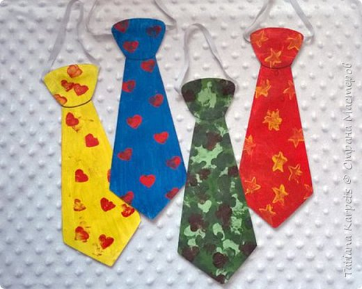 """Делать подарки к праздникам своими руками уже стало доброй традицией в нашей семье. На этот раз для наших любимых дедушек, папы и дяди мы с дочкой смастерили вот такие забавные галстуки.   Для этого нам понадобилось: белая плотная бумага, краски """"гуашь"""", кисточки, клей, шаблон галстука, 2 кусочка ластика, эластичная лента (резинка), ножницы и клей. Итак, на белой плотной бумаге мы распечатали шаблоны галстука, раскрасили наши заготовки и дали им высохнуть. В это время из кусочков ластика сделали штампики. Галстук зелёного цвета мы раскрашивали пальчиками, а на все остальные нанесли рисунок с помощью штампиков. Снова дали краске высохнуть. Аккуратно по контуру вырезали наши будущие """"шедевры"""", с оборотной стороны приклеили резинку. Приклеили галстуки на плотный лист белой бумаги и вырезали.  Вот и всё, подарки готовы!  фото 1"""