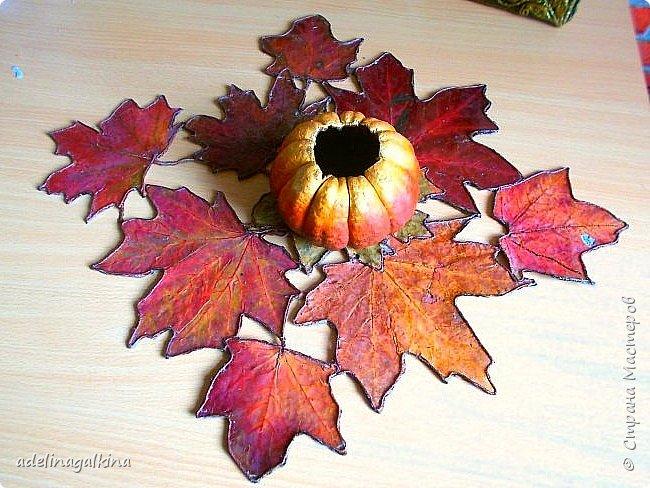 Здравствуйте , дорогие мастера и мастерицы! Осенью собрала немного сухих листьев и сначала хотела их применить при создании панно или сделать из них корзинку. Разрезала упаковку для молока, разгладила и приклеила листья , утюгом прогладила. Покрыла бесцветным лаком и оставила. Попробовала сделать корзину , не получилось.  Увидела в интернете декоративную салфетку из листьев, но как её делали не нашла. Листьев больше не было. Тогда я осторожно отодрала листья с картона от корзинки ( при этом , конечно повредила их, а также изменился цвет, т.к пришлось размачивать в воде.) Но делать нечего. Приклеила их на плотную ткань, электроважегателем вырезала вокруг листьев, по краям приклеила шнур макраме, вновь покрыла лаком. Всё. Думаю осенью повторю уже с неиспорченными листьями.  Вазу в центре сделала из тыквочки, которую удалось высушить осенью. Просто покрасила её.       фото 1