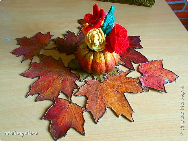 Здравствуйте , дорогие мастера и мастерицы! Осенью собрала немного сухих листьев и сначала хотела их применить при создании панно или сделать из них корзинку. Разрезала упаковку для молока, разгладила и приклеила листья , утюгом прогладила. Покрыла бесцветным лаком и оставила. Попробовала сделать корзину , не получилось.  Увидела в интернете декоративную салфетку из листьев, но как её делали не нашла. Листьев больше не было. Тогда я осторожно отодрала листья с картона от корзинки ( при этом , конечно повредила их, а также изменился цвет, т.к пришлось размачивать в воде.) Но делать нечего. Приклеила их на плотную ткань, электроважегателем вырезала вокруг листьев, по краям приклеила шнур макраме, вновь покрыла лаком. Всё. Думаю осенью повторю уже с неиспорченными листьями.  Вазу в центре сделала из тыквочки, которую удалось высушить осенью. Просто покрасила её.       фото 2