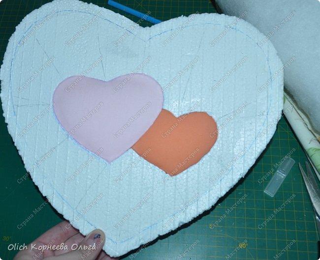 Здравствуйте. Хочу показать, как я при помощи ткани, пенопласта, синтепона, клея и разных украшалок преобразила совершенно обычную коробку хоть и необычной формы -  формы сердца. В этой коробке будет лежать подарок для дорогого человека, поэтому хотелось при помощи нежных оттенков ткани, множества складочек, сердечек, кружева и полубусин добавить упаковке  уюта, мягкости и красоты. А после эту коробку можно будет использовать для хранения всевозможных вещей. фото 13