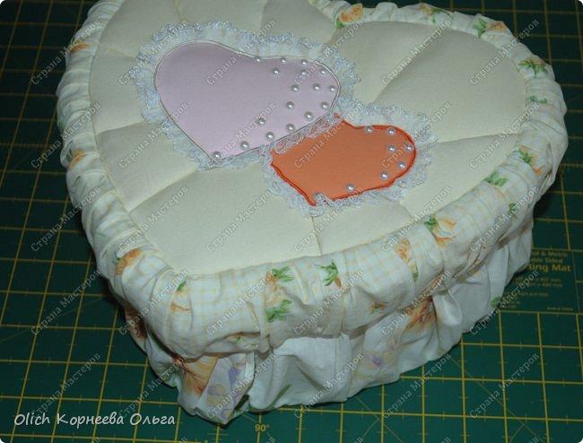 Здравствуйте. Хочу показать, как я при помощи ткани, пенопласта, синтепона, клея и разных украшалок преобразила совершенно обычную коробку хоть и необычной формы -  формы сердца. В этой коробке будет лежать подарок для дорогого человека, поэтому хотелось при помощи нежных оттенков ткани, множества складочек, сердечек, кружева и полубусин добавить упаковке  уюта, мягкости и красоты. А после эту коробку можно будет использовать для хранения всевозможных вещей. фото 33