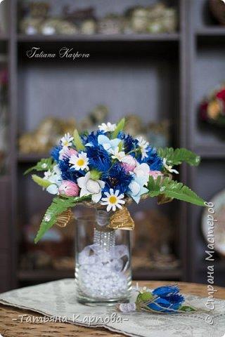 «…Цьвяток радзiмы васiлька!» Легенда: букет-символ в национальном стиле.  То, о чем молчит девушка, скажут за нее цветы…  Главным акцентом букета являются чистый синий цвет василька – это символ верности и чистоты, постоянства и духовности. Цветок клевера означает связь поколений. Ромашка символ радости и доброты. Простота и чистота этих цветов также ассоциируется с юностью и невинностью. Колокольчик тоже цветок радости и оберег. Наряду с соломенными колокольчиками оберегают молодую семью от неприятностей, злых духов. Пять маленьких колокольчиков по кругу символизируют семью и продолжение рода.  Букет и бутоньерка олицетворяют объединение любящих сердец! Описание работы: материалы - льняная бечёвка, гофра, кружево и стразы, соломенные колокольчики, искусственная зелень. конфеты: Марсианка, карамель с начинкой, общее количество 25 шт  Размер букета: высота 30 см, диаметр 22 см.  Техника исполнения: свит-дизайн, макраме фото 1