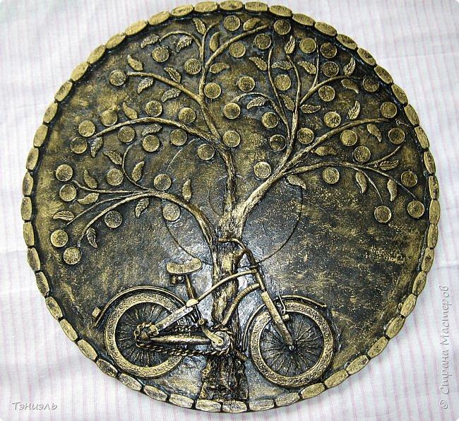 Всем доброго времени суток! Вот такой маленький велосипед на большом виниловом диске получился. диски покупаю в антикваре по 10 руб за штуку. Очень торопилась, не успела сфотографировать не покрашенным. Постараюсь рассказать. Ствол и веточки сделаны из бумажных салфеток, листочки и монетки от ёлочных гирлянд. Рамка, или как её назвать, это разобранная деревянная салфетка под горячее, разноцветная такая из фикс- прайса. фото 1