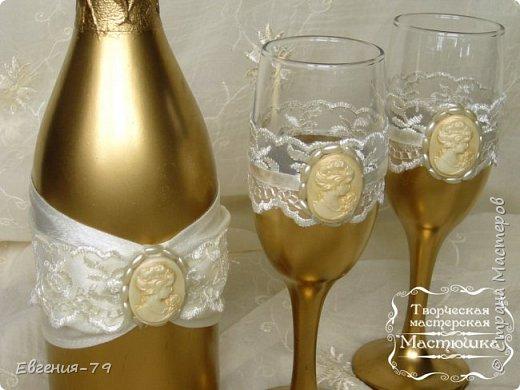 Бутылка и бокалы декорирована с помощью золотого спрея, наклеены щелковые ленты, капроновое кружево. Центральный элемент камея выполнен из полимерной глины, с помощью молда, тонирован зотоистыми тенями. Вокруг камеи пришиты бусины. фото 2