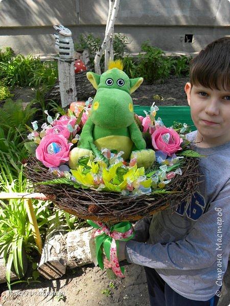 """Здравствуйте! Сегодня хочу показать вам сладкий букет с игрушкой, который сотворился на заказ в подарок семилетней девочке. Он получился достаточно весомым, диаметр его примерно 60 см. Девочка очень любит динозавриков, отсюда и идея создания такого букета. Зеленой сизалью и ветками березы, сплетенными в кольцо, обозначила гнездо динозавра, в котором сидит сам динозаврик со своим яйцом-детенышем (киндер-сюрприз). Украсила гнездо розами с киндер-сюрпризами внутри и фантазийными цветами, внутрь которых поместила шоколадные конфеты """"Детский сувенир"""". Добавила небольшие веточки с леденцовой карамелью """"Fruit"""".  фото 3"""