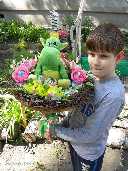 """Здравствуйте! Сегодня хочу показать вам сладкий букет с игрушкой, который сотворился на заказ в подарок семилетней девочке. Он получился достаточно весомым, диаметр его примерно 60 см. Девочка очень любит динозавриков, отсюда и идея создания такого букета. Зеленой сизалью и ветками березы, сплетенными в кольцо, обозначила гнездо динозавра, в котором сидит сам динозаврик со своим яйцом-детенышем (киндер-сюрприз). Украсила гнездо розами с киндер-сюрпризами внутри и фантазийными цветами, внутрь которых поместила шоколадные конфеты """"Детский сувенир"""". Добавила небольшие веточки с леденцовой карамелью """"Fruit"""".  фото 2"""