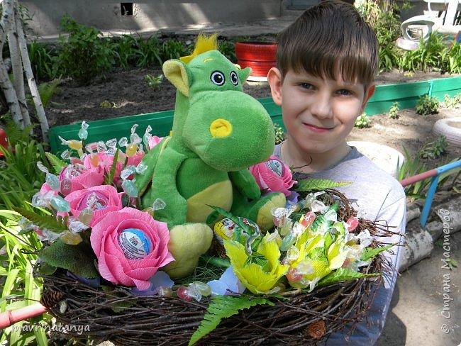 """Здравствуйте! Сегодня хочу показать вам сладкий букет с игрушкой, который сотворился на заказ в подарок семилетней девочке. Он получился достаточно весомым, диаметр его примерно 60 см. Девочка очень любит динозавриков, отсюда и идея создания такого букета. Зеленой сизалью и ветками березы, сплетенными в кольцо, обозначила гнездо динозавра, в котором сидит сам динозаврик со своим яйцом-детенышем (киндер-сюрприз). Украсила гнездо розами с киндер-сюрпризами внутри и фантазийными цветами, внутрь которых поместила шоколадные конфеты """"Детский сувенир"""". Добавила небольшие веточки с леденцовой карамелью """"Fruit"""".  фото 5"""