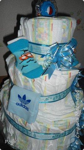 Срочно попросили сделать подарок на рождение малыша. Изобразила вот такой тортик. 3 яруса, памперсы использовала Pampers Premium Care 3 (5-9 кг) 60 шт.сворачивала веером. Ленты очень красивые одна голубая с надписями, вторая, как подложка морского цвета. Ну и детские мелочи погремушка носочки, шапочка и т.д. Упаковывала в слюду 2м*70 см. Сделала практически за 2 часа. фото 4