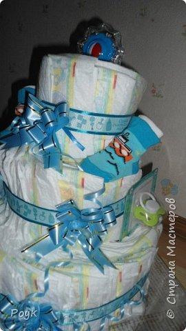 Срочно попросили сделать подарок на рождение малыша. Изобразила вот такой тортик. 3 яруса, памперсы использовала Pampers Premium Care 3 (5-9 кг) 60 шт.сворачивала веером. Ленты очень красивые одна голубая с надписями, вторая, как подложка морского цвета. Ну и детские мелочи погремушка носочки, шапочка и т.д. Упаковывала в слюду 2м*70 см. Сделала практически за 2 часа. фото 6