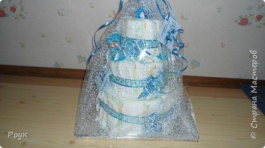 Срочно попросили сделать подарок на рождение малыша. Изобразила вот такой тортик. 3 яруса, памперсы использовала Pampers Premium Care 3 (5-9 кг) 60 шт.сворачивала веером. Ленты очень красивые одна голубая с надписями, вторая, как подложка морского цвета. Ну и детские мелочи погремушка носочки, шапочка и т.д. Упаковывала в слюду 2м*70 см. Сделала практически за 2 часа. фото 1