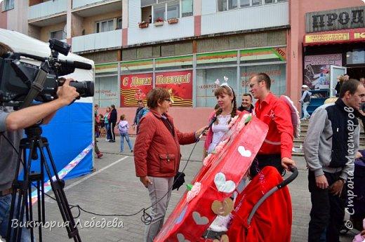 Здравствуйте, жители Страны Мастеров. Парад колясок, в котором мы участвовали, был в прошлом году. Но скоро в каждом городе они пройдут опять, и ,может, какой-нибудь семье мы поможем с идеей для вдохновения. Мы живем в самом западном регионе страны - в Калининградской области, городе Гвардейке. Парад проходил в День Города, и поэтому, мы решили выразить любовь нашему городу в форме сердца коляски. Сам процесс частично был сфотографирован, но материалы пропали. Остались только фотографии мероприятия. Скажу только, что сердце вырезали из больших коробок( от холодильника, склеивались между собой тоже картонными коробками, затем всё сердце обклеивали самоклеящаейся плёнкой, украшали цветами из салфеток, вырезанными буквами из плёнки той же, а также обтянули красной тканью колясочку. фото 8