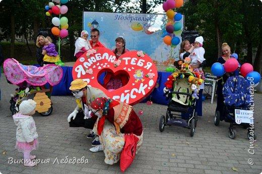Здравствуйте, жители Страны Мастеров. Парад колясок, в котором мы участвовали, был в прошлом году. Но скоро в каждом городе они пройдут опять, и ,может, какой-нибудь семье мы поможем с идеей для вдохновения. Мы живем в самом западном регионе страны - в Калининградской области, городе Гвардейке. Парад проходил в День Города, и поэтому, мы решили выразить любовь нашему городу в форме сердца коляски. Сам процесс частично был сфотографирован, но материалы пропали. Остались только фотографии мероприятия. Скажу только, что сердце вырезали из больших коробок( от холодильника, склеивались между собой тоже картонными коробками, затем всё сердце обклеивали самоклеящаейся плёнкой, украшали цветами из салфеток, вырезанными буквами из плёнки той же, а также обтянули красной тканью колясочку. фото 6