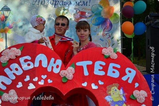Здравствуйте, жители Страны Мастеров. Парад колясок, в котором мы участвовали, был в прошлом году. Но скоро в каждом городе они пройдут опять, и ,может, какой-нибудь семье мы поможем с идеей для вдохновения. Мы живем в самом западном регионе страны - в Калининградской области, городе Гвардейке. Парад проходил в День Города, и поэтому, мы решили выразить любовь нашему городу в форме сердца коляски. Сам процесс частично был сфотографирован, но материалы пропали. Остались только фотографии мероприятия. Скажу только, что сердце вырезали из больших коробок( от холодильника, склеивались между собой тоже картонными коробками, затем всё сердце обклеивали самоклеящаейся плёнкой, украшали цветами из салфеток, вырезанными буквами из плёнки той же, а также обтянули красной тканью колясочку. фото 9