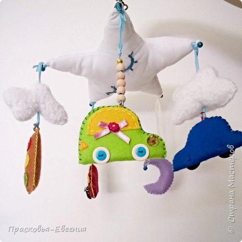 Это мой второй мобиль в подарок знакомым. Каруселька предназначается мальчику, поэтому игрушками стали опять машинки. Дополнительно разбавила декор тучками и месяцем. Крестовина сделана из палочек лаврового дерева - на счастье хозяину. Покрашены палочки акриловой краской белый перламутровый, чтобы дерево было видно. фото 5