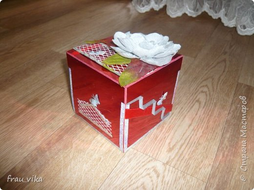 Коробка выполнена в красно - серебряной цветовой гамме. Сверху обклеена красным фольгированным картоном. На каждой стороне символично обозначены пожелания имениннице. На этом фото: букет - будь любима, бантик - будь красива. Крышка. Самодельный цветок из гофробумаги серебристой. Листья от декоративных тканевых цветов. Серебристая сетка, на которой сидит бабочка. Такая же бабочка сидит на красной тонкой ленте. Бабочки тканевые. фото 2