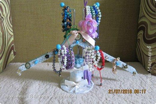 Вот такую подставку для браслетов сделал для своей супруги. Подставка выполнена из подставки под кружки, деревянной вешалки, кружевной ткани, ленточек, деревянных дюбелей и бижутерии. Покрашено голубой и золотой краской.  фото 6