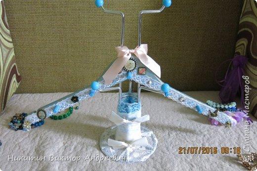 Вот такую подставку для браслетов сделал для своей супруги. Подставка выполнена из подставки под кружки, деревянной вешалки, кружевной ткани, ленточек, деревянных дюбелей и бижутерии. Покрашено голубой и золотой краской.  фото 1