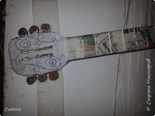 Гитара изготовлена на подарок для музыканта, мастер класса не нашла, поэтому решила поделиться с вами, может кому-то пригодиться. Основа из картона обклеенная газетами, украшена салфеточными жгутиками, покрашена колер бронзовый порошок  и лак акриловый. фото 13