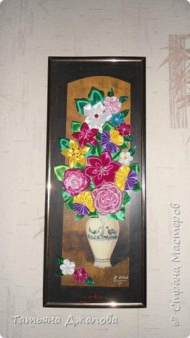 Привет всем жителям страны!!! Давно хотелось смастерить что-нибудь из канзаши, попробовала сделать цветочек, понравилось, захотелось сделать ещё и так набралось несколько.Так как у меня сыновья, заколочки делать не для кого, решила сделать панно-картину. Так как нетерпелось все это воплотить в жизнь, взяла за основу готовую картину и прямо на стекло наклеила свои цветы. Остатками цветов украсила фотографии родных. Не судите строго я только учусь!!!! фото 1