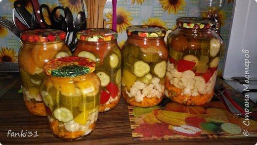 Вот такое ассорти из моркови, пару долек чеснока, цветной капусты, паприки, огурцов и помидор.  В банки раскладываем зелень, лавровый лист, перцы, гвоздику. Затем произвольно или слоями укладываем овощи. Для маринада в кипящей воде растворяем соль и сахар. В конце добавляем уксус и заливаем маринадом ассорти овощное в банке. Стерилизуем 3-х литровые банки 25-30 минут. Литровые – 15 минут. Закрываем банки и переворачиваем до полного остывания. Консервированное овощное ассорти готово. Приятного аппетита! фото 1