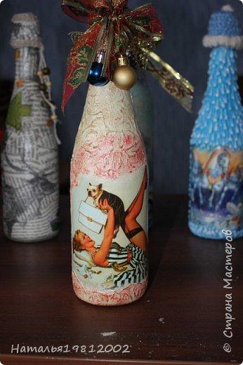 Здравствуйте Мастерицы! Это мои первые Новогодние бутылочки. Подготовила бутылку, покрасила белой акриловой краской, приклеила на клей ПВА-универсальный истонченную открытку, которую сначала покрыла на 3 слоя лаком затем истончила (у открыток внутренний слой можно просто отслоить, подцепляю ногтем с угла открытки и отдираю сколько могу. Затем на уже не глянцевый слой кисточкой наношу воду на часть открытки и пальчиком начинаю истончать скатывающим движением, а дальше, по наитию поймете, что уже хватить истончать, а то открытка порвется). Далее по свободным местам и чуть захватывая открытку, ватной палочкой, размазала клей момент, который для плиток (позже выложу фото используемых материалов), после высыхания нанесла губкой цвет что-то между желтым и бежевы. Далее губкой легкими, тыкающими движениями нанесла еще два оттенка (не помню какие, цвета кажется просто золото и еще какое-то золото, может медь, не помню). После высыхания покрыла аквалаком  на 3 слоя. Крышечку делала из оставшейся от бутылки обертки-фольги, которой придала форму колпачка, на нее приклеила термопистолетом золотую тканевую сетку с новогодней лентой и новогодними шариками. фото 1