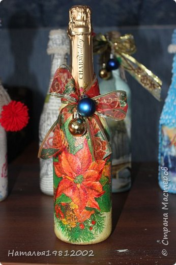 Здравствуйте Мастерицы! Это мои первые Новогодние бутылочки. Подготовила бутылку, покрасила белой акриловой краской, приклеила на клей ПВА-универсальный истонченную открытку, которую сначала покрыла на 3 слоя лаком затем истончила (у открыток внутренний слой можно просто отслоить, подцепляю ногтем с угла открытки и отдираю сколько могу. Затем на уже не глянцевый слой кисточкой наношу воду на часть открытки и пальчиком начинаю истончать скатывающим движением, а дальше, по наитию поймете, что уже хватить истончать, а то открытка порвется). Далее по свободным местам и чуть захватывая открытку, ватной палочкой, размазала клей момент, который для плиток (позже выложу фото используемых материалов), после высыхания нанесла губкой цвет что-то между желтым и бежевы. Далее губкой легкими, тыкающими движениями нанесла еще два оттенка (не помню какие, цвета кажется просто золото и еще какое-то золото, может медь, не помню). После высыхания покрыла аквалаком  на 3 слоя. Крышечку делала из оставшейся от бутылки обертки-фольги, которой придала форму колпачка, на нее приклеила термопистолетом золотую тканевую сетку с новогодней лентой и новогодними шариками. фото 7