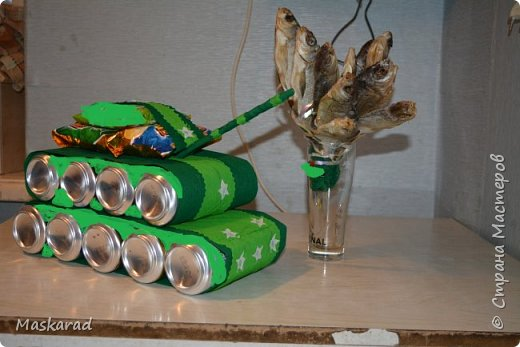 """Примерная конструкция взята с просторов интернета, автора не знаю, я танк немного модернизировала, добавив второй ряд """"колес"""" Использовала: картон, гофрированную бумагу двух оттенков (темный и светло зеленый), кусочек белой бумаги, ненужный карандаш (можно коктейльную трубочку) для пушки. А так же напитки, сухарика, рыбу. фото 1"""