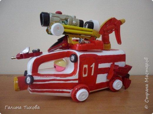 """Вот такую пожарную машину можно сделать из бросового материала. В её изготовлении использованы пластиковый контейнер из под моющего средства, пулевизатор, крышки от молочных контейнеров, лом от детских игрушек, красная акриловая краска, клей """"Титан""""."""