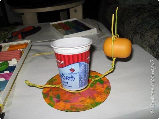 Осень, время поделок из природного материала...  Ёжик у пенька с грибами. В основе пенька пластиковый стаканчик от мороженого, и облеплен пластилином, мох; ёжик - киндер обмазан пластилином и украшен семенами подсолнечника; грибы (должны были быть опята, из палочек и шляпок от желудей, но в виду их отсутствия вышли другие грибочки) - березовые палочки, пластилин и скорлупа грецких орехов; в основании всей композиции диск компьютерный. фото 16
