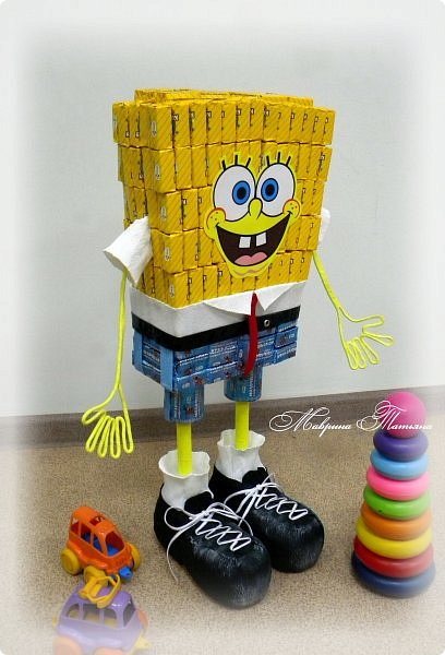 """Здравствуйте! Сегодня вашему вниманию хочу представить Губку Боба - квадратные штаны. Делался в подарок пятилетнему мальчишке буквально на одном дыхании. В нем около 3,5 кг сладостей и ростом он выше 50 см. Использовала конфеты двух цветов: желтые - """"Конфета на сливках"""", синие - """"Молочная конфета с кунжутом"""". фото 5"""