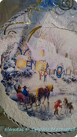 Доброй ночи,Страна!!! Совсем скоро мы будем праздновать любимый праздник. Новый год. Я люблю готовить подарки заранее. Вот и сейчас хочу предложить вашему вниманию несколько панно.  Первое панно сделано на панно из магазина фикс прайс.Покрыла основание краской,наклеила распечатку, сверху на дома,деревья и по краю нанесла состав, имитирующий снег и все покрыла лаком с блестками. На основание подвеса прикрепила бантик, который сделан из ленты из магазина фикс прайс. фото 2