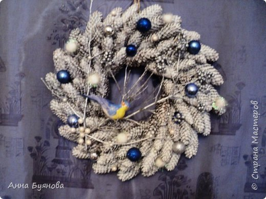 Классический веночек из еловых шишек окрашен в белый цвет. На ветку кустарника, окрашенной серебристой краской,  присела крохотная синичка.Венок уррашен маленькими шарами, жемчужинками.