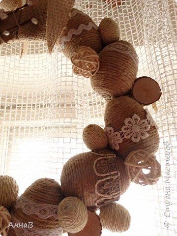 Увидела в магазине для рукоделия половинки яиц из пенопласта, возникла идея сделать пасхальный венок в эко-стиле. Яичные заготовки обмотала шпагатом разного цвета и толщины, декор - тесьма, кружево. Основа для венка - круг из плотного картона, обмотка - бумажный пакет. Веточка вербы - готовая. В качестве дополнительного декора использовала маленькие шарики из ротанага и спилы дерева - все готовое, приобрела также в магазине для рукоделия. фото 3