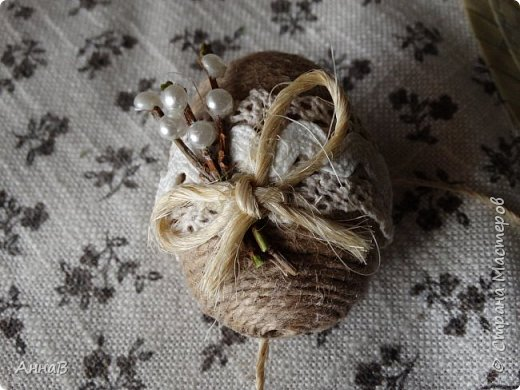 Увидела в магазине для рукоделия половинки яиц из пенопласта, возникла идея сделать пасхальный венок в эко-стиле. Яичные заготовки обмотала шпагатом разного цвета и толщины, декор - тесьма, кружево. Основа для венка - круг из плотного картона, обмотка - бумажный пакет. Веточка вербы - готовая. В качестве дополнительного декора использовала маленькие шарики из ротанага и спилы дерева - все готовое, приобрела также в магазине для рукоделия. фото 11