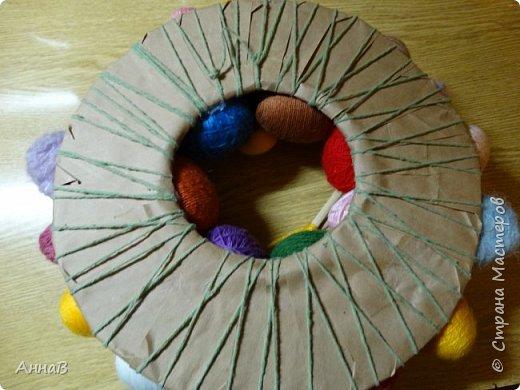 Увидела в магазине для рукоделия половинки яиц из пенопласта, возникла идея сделать пасхальный венок в эко-стиле. Яичные заготовки обмотала шпагатом разного цвета и толщины, декор - тесьма, кружево. Основа для венка - круг из плотного картона, обмотка - бумажный пакет. Веточка вербы - готовая. В качестве дополнительного декора использовала маленькие шарики из ротанага и спилы дерева - все готовое, приобрела также в магазине для рукоделия. фото 14