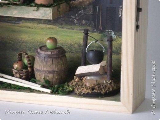 """В последнее время меня очень привлекает создание миниатюр. Нравится придумывать различные сюжеты и композиции, используя при этом миниатюрные предметы. В этот раз мне захотелось сделать миниатюру, связанную с темой """"Деревня"""". За основу был взят румбокс, внутри которого были размещены: домик, деревянное ведерко, корзиночка с яблоками, деревянная бочка, котелок на костре, вилы и коса. А в качестве фона для задней стенки румбокса я взяла одну из моих любимейших фотографий о Норвегии. В принципе, с этой фотографии все и началось, в смысле возникновения самой идеи. Моя композиция прежде всего для тех, кто любит украшать свой дом подобного рода предметами. Румбокс хорошо впишется , скажем, в прихожей, или на кухне, а кто-то найдет место и в комнате. Кстати, румбокс можно вешать на стену, а можно просто поставить на полку, это кому как понравится. Главное, что свою работу я сделала с душой.  И несколько слов о фотографиях данной миниатюры. Румбокс со стеклянной дверцей, при фотографировании стекло бликует,  и не все хорошо видно. Именно поэтому пришлось снимать частями, чтобы хорошо было видно внутреннюю композицию. фото 2"""