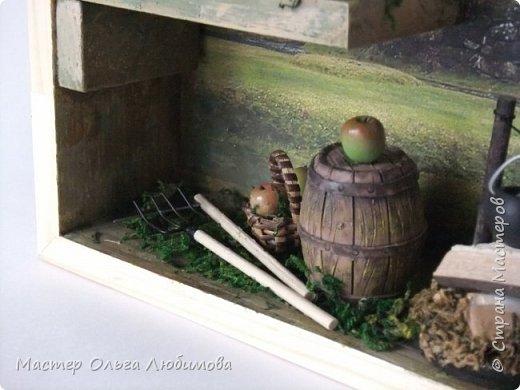 """В последнее время меня очень привлекает создание миниатюр. Нравится придумывать различные сюжеты и композиции, используя при этом миниатюрные предметы. В этот раз мне захотелось сделать миниатюру, связанную с темой """"Деревня"""". За основу был взят румбокс, внутри которого были размещены: домик, деревянное ведерко, корзиночка с яблоками, деревянная бочка, котелок на костре, вилы и коса. А в качестве фона для задней стенки румбокса я взяла одну из моих любимейших фотографий о Норвегии. В принципе, с этой фотографии все и началось, в смысле возникновения самой идеи. Моя композиция прежде всего для тех, кто любит украшать свой дом подобного рода предметами. Румбокс хорошо впишется , скажем, в прихожей, или на кухне, а кто-то найдет место и в комнате. Кстати, румбокс можно вешать на стену, а можно просто поставить на полку, это кому как понравится. Главное, что свою работу я сделала с душой.  И несколько слов о фотографиях данной миниатюры. Румбокс со стеклянной дверцей, при фотографировании стекло бликует,  и не все хорошо видно. Именно поэтому пришлось снимать частями, чтобы хорошо было видно внутреннюю композицию. фото 3"""