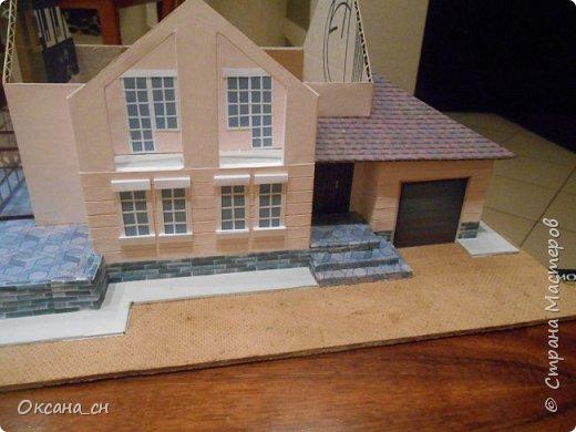 Дорогие мастера, хочу предложить небольшой МК по изготовлению макета загородного дома. Жилой дом изготовлен из картона и представляет собой двухэтажный дом с балконом, террасой, зимним садом, гаражом и выходами с двух сторон. Проект дома я взяла здесь: http://piterplan.ru/projects-of-the-houses-from-concrete/projects-2-floors/4643-nadejda-123pp.html Чтобы изготовить макет загородного жилого дома нам необходимо иметь: лист ДВП размером 45 х 32 см, толстый картон из ящиков, белый картон, двустороннюю бумагу вишневого и сине-серого цветов, распечатанные фактуры камня на фундамент, брусчатки, плитки на террасу, черепицы на крышу, водоэмульсионную краску розового цвета, канцелярский нож, клей «Титан», линейка, карандаш. Можно приступать к работе... фото 12
