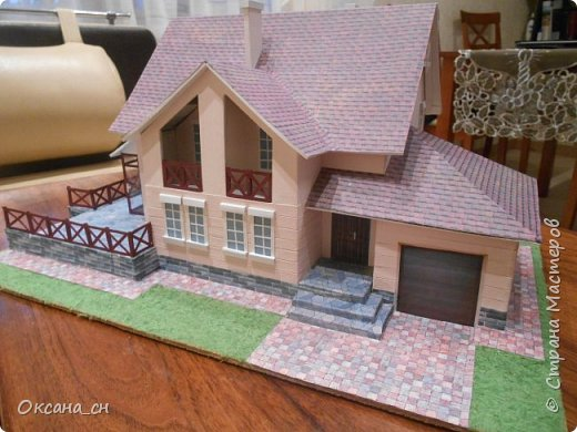 Дорогие мастера, хочу предложить небольшой МК по изготовлению макета загородного дома. Жилой дом изготовлен из картона и представляет собой двухэтажный дом с балконом, террасой, зимним садом, гаражом и выходами с двух сторон. Проект дома я взяла здесь: http://piterplan.ru/projects-of-the-houses-from-concrete/projects-2-floors/4643-nadejda-123pp.html Чтобы изготовить макет загородного жилого дома нам необходимо иметь: лист ДВП размером 45 х 32 см, толстый картон из ящиков, белый картон, двустороннюю бумагу вишневого и сине-серого цветов, распечатанные фактуры камня на фундамент, брусчатки, плитки на террасу, черепицы на крышу, водоэмульсионную краску розового цвета, канцелярский нож, клей «Титан», линейка, карандаш. Можно приступать к работе... фото 19