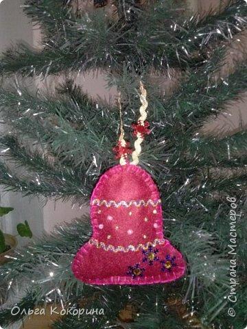 На Новый год или Рождество можно сделать ёлочные украшения своими руками! Пусть новый год еще далеко, но как говорят, готовь сани летом! Нам понадобиться фетр любого цвета, ножницы, бусинки, красивые ленточки для украшения, нитки, иголка.  готовим шаблон для будущей игрушки. Я выбрала форму колокольчика. Вырезаем из фетра две детали. фото 6