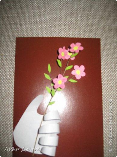 Доброго времени суток! Представляю Вашему вниманию очередное творение. Цветы - скорлупки от фисташек, веточка - завязанный на много узлов старый шнурок из ботинка. Всё приклеила на тонкий картон, цветы подкрасила гуашью, верединки-бисер. На лепестках кое-где приклеены прозрачные бисеренки,как капельки росы ( на фото их не очень видно). Интересно получилось с золотой бумажкой, окаймляющей картинку. Такой бумажки у меня не нашлось. Решила использовать упаковку от цветов, но она была помята.Самое простое решение - утюг. А упаковка эта не разгладилась а съёживаться начала от температуры. Посмотрела - так даже интереснее получается. Съёжила всё, что осталось, приклеила. фото 13